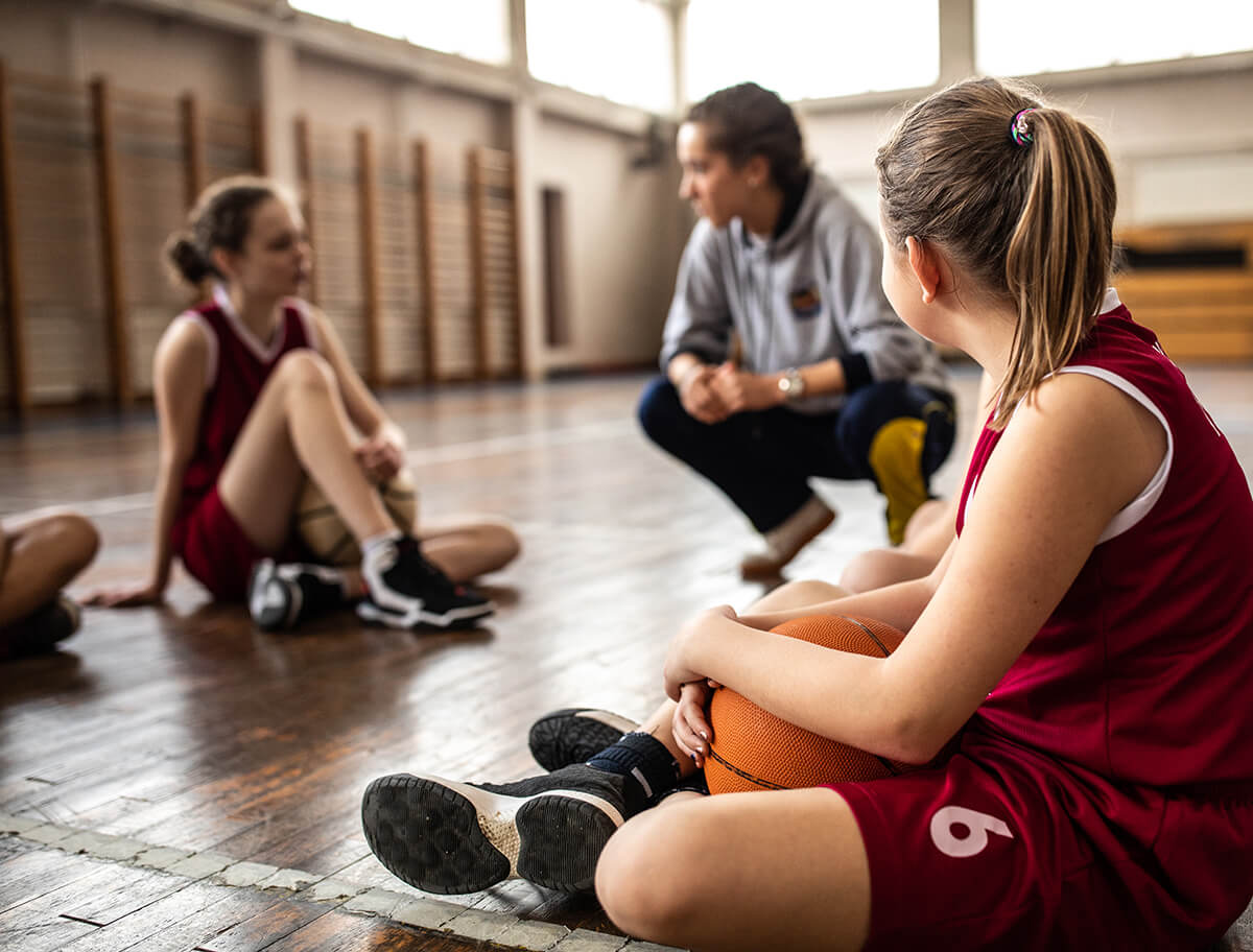 2 teenage girls in basketball uniforms, one holding a basket ball, are sitting on the floor with their coach, an adult woman kneeling beside them. They are having a conversation.