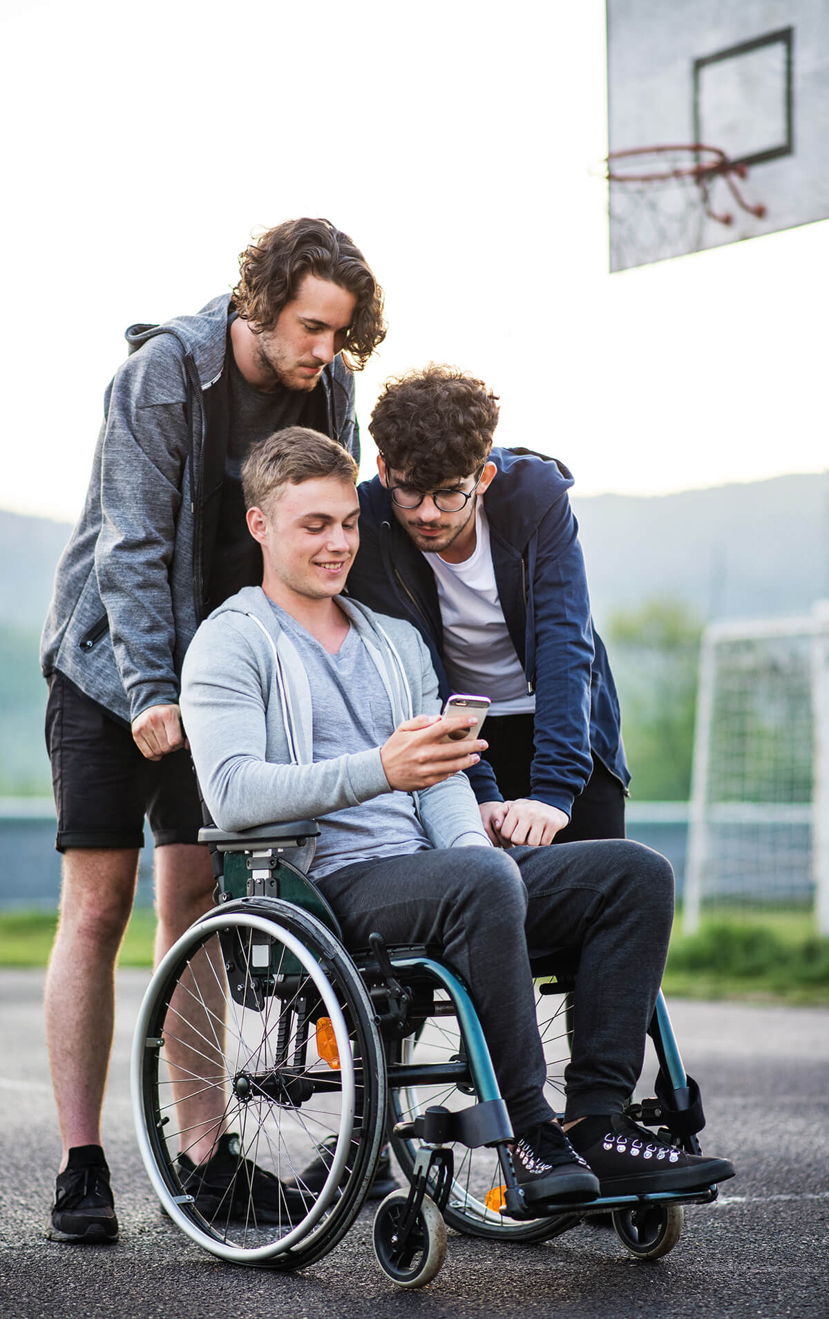 Three teenage boys are on a basketball court and looking at the phone that one boy is holding. The boy holding the phone is in a wheelchair.