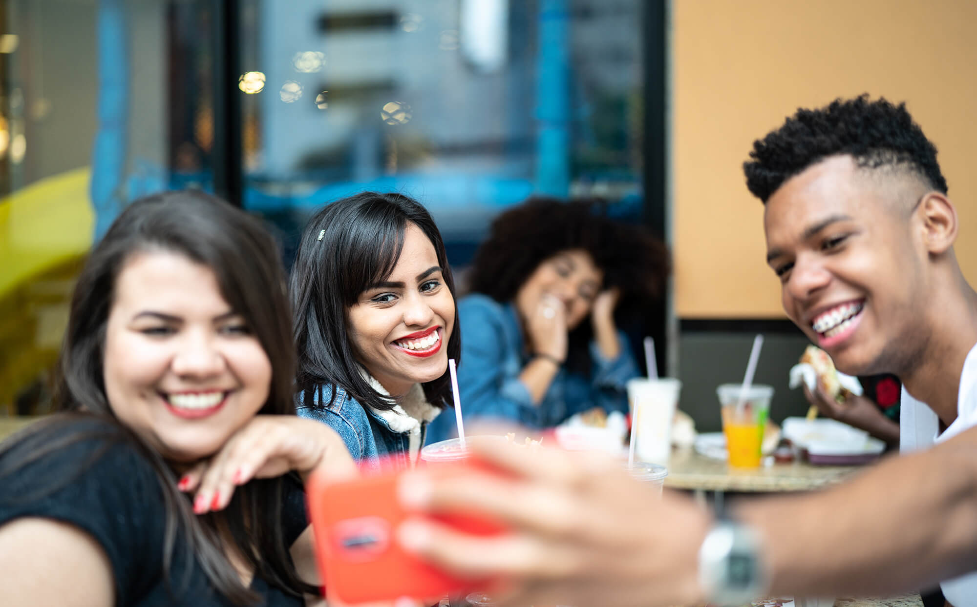 3 teens in the foreground, and one blurred out in the background, are sitting at a table in a restaurant. One teen who has braces on his teeth, is holding a phone out to take a selfie of himself and the other teens. They are all smiling and look very happy.