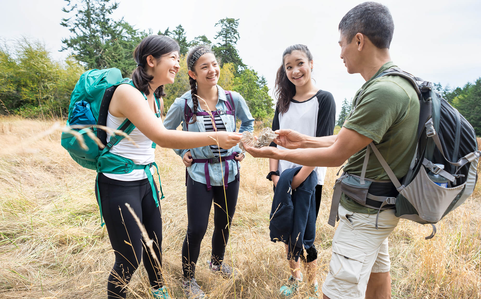 3 teenage girls are in a meadow with an adult man who appears to be an outdoor educator. They are examining something that the educator is holding in his hands that appears to be something found in nature. They are wearing backpacks and hiking gear.