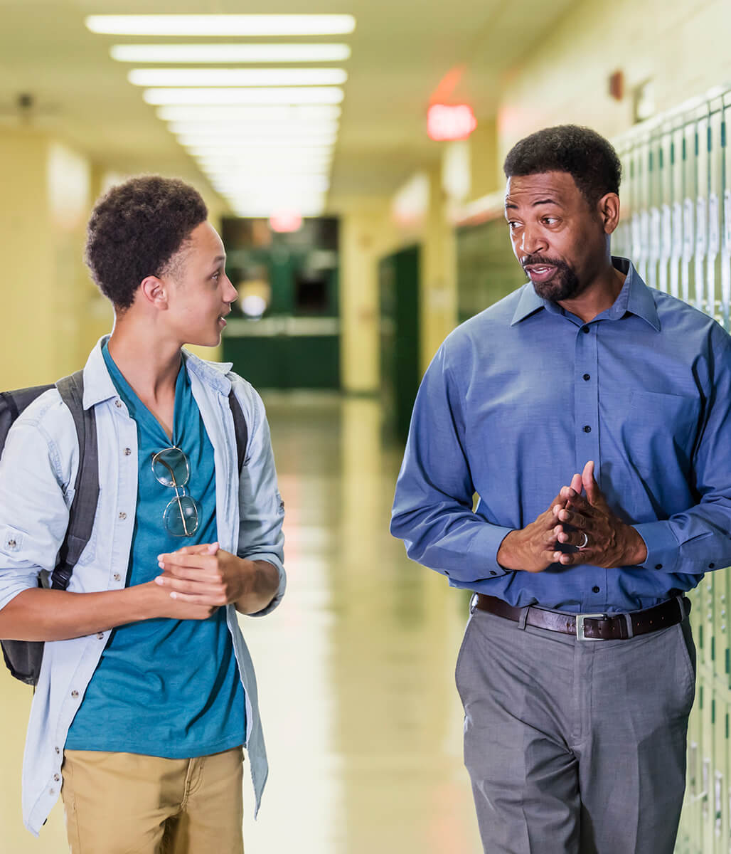 A teenage boy and adult man, likely his teacher, are walking down the hall of a high school, with lockers to the right. They are talking to each other in a respectful manner.